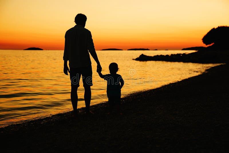 Vader en zoons achtersilhouetten die door het overzees lopen royalty-vrije stock afbeeldingen