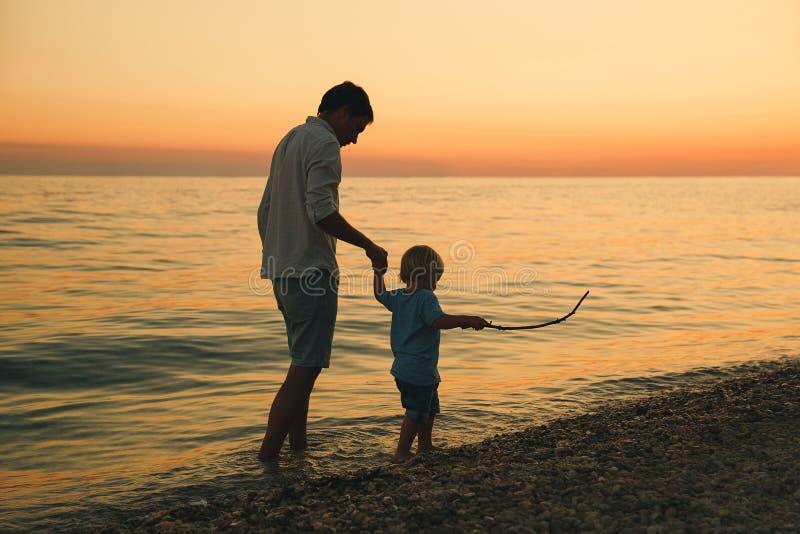Vader en zoons achtersilhouetten die door het overzees lopen stock foto