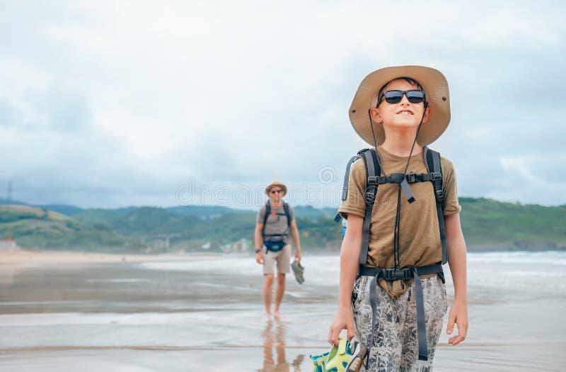 Vader en zoons backpacker reizigersgang op zand oceaanstrand royalty-vrije stock foto