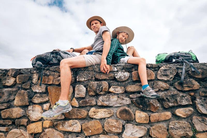Vader en zoons backpacker reizigersrust die samen op oud zitten royalty-vrije stock afbeeldingen