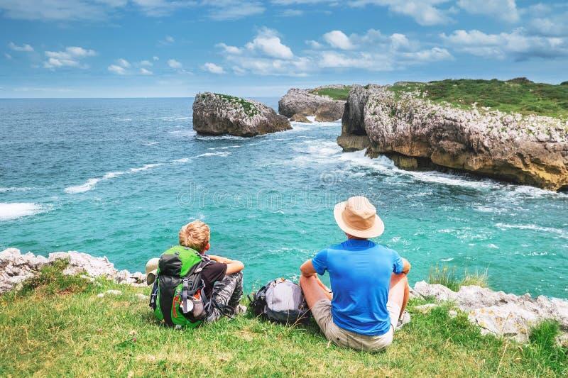 Vader en zoons backpacker reizigersrust op het rotsachtige overzees zija stock foto
