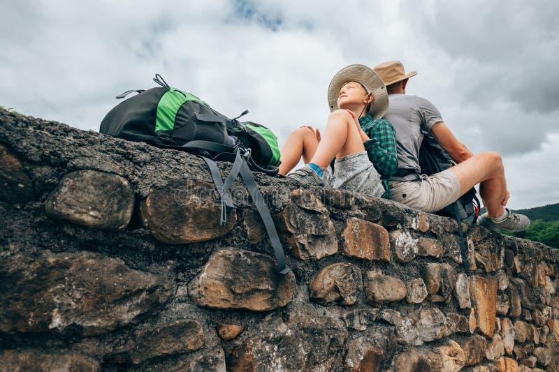 Vader en zoons backpacker reizigersrust samen op oude steen wa stock afbeeldingen