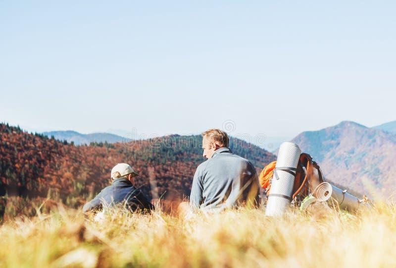Vader en zoons de reizigers rusten samen in bergvallei met mooie heuvelsmening stock afbeelding
