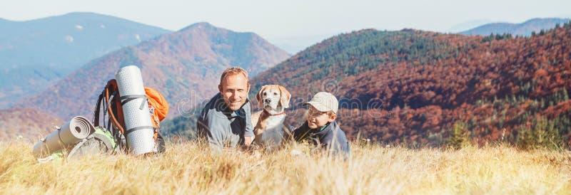 Vader en zoons de rust van backpackerswandelaars op bergheuvel met stock fotografie