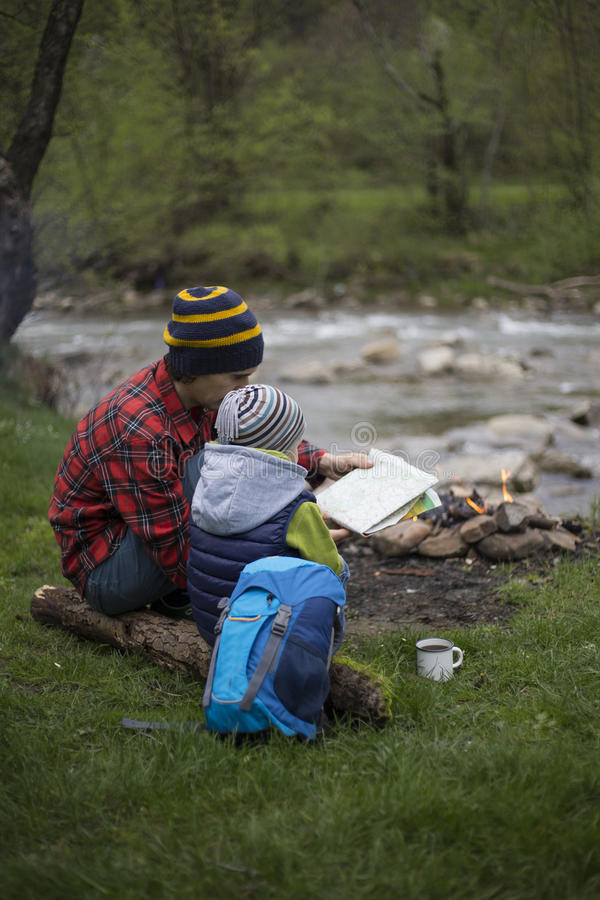 Vader en zoons de zitting dichtbij een kampvuur bij het kampeerterrein en is l royalty-vrije stock foto