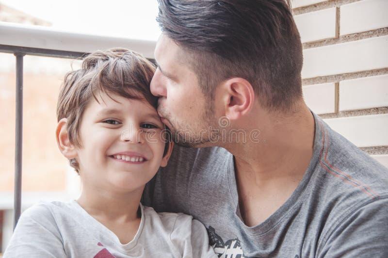 Vader en zoons emotionele steun en manifestatie van liefde, supp stock foto