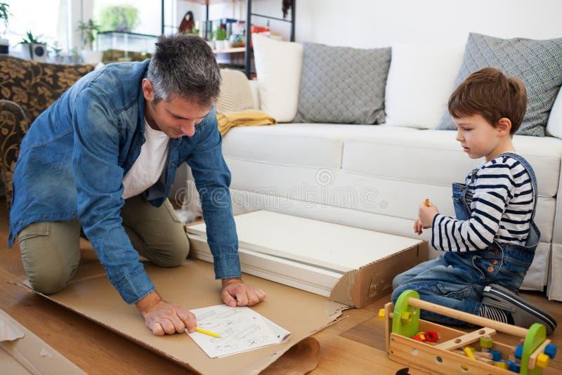 Vader en zoons het assembleren meubilair stock afbeelding