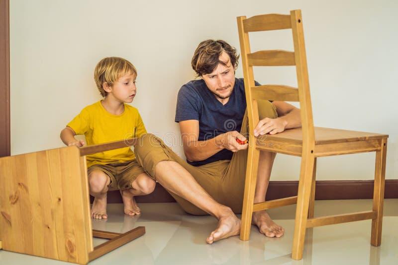Vader en zoons het assembleren meubilair Jongen die zijn papa thuis helpen Gelukkig familieconcept stock afbeeldingen