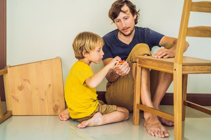 Vader en zoons het assembleren meubilair Jongen die zijn papa thuis helpen Gelukkig familieconcept stock foto's