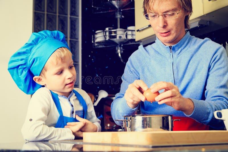 Vader en zoons het koken in keuken stock foto's