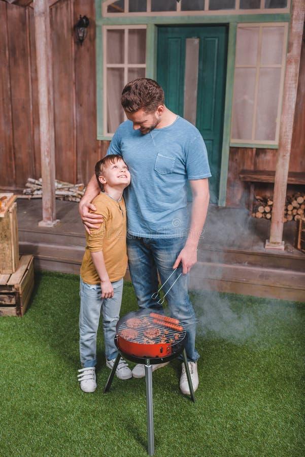 Vader en zoons het koken rundvleesburgers en hotdogworsten op barbecue stock fotografie