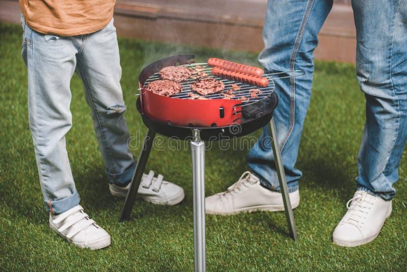 Vader en zoons het koken rundvleesburgers en hotdogworsten op barbecue stock foto's