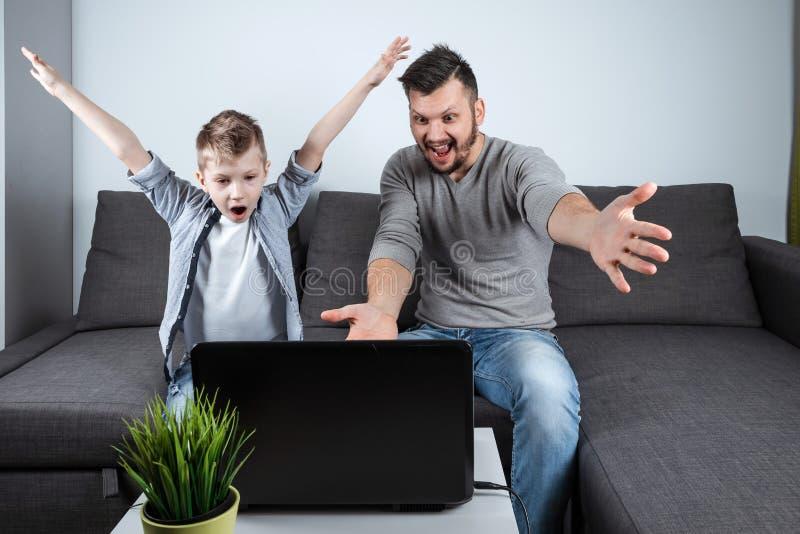 Vader en zoons het letten op voetbal in laptop thuis Emotionele mens en jongen, die favoriet team toejuichen Het concept familie stock foto's