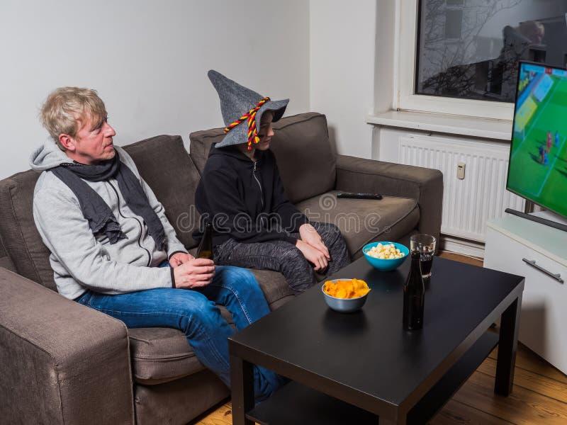 Vader en zoons het letten op het voetbal van de voetbalwereldbeker op TV royalty-vrije stock fotografie