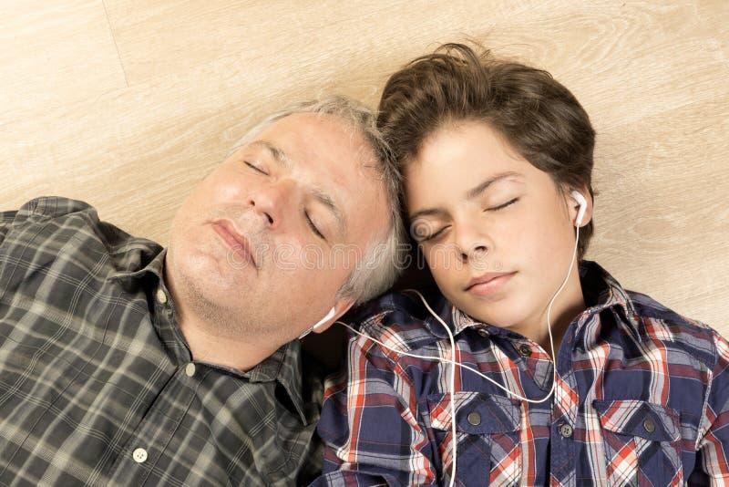 Vader en zoons het luisteren muziek samen stock foto's