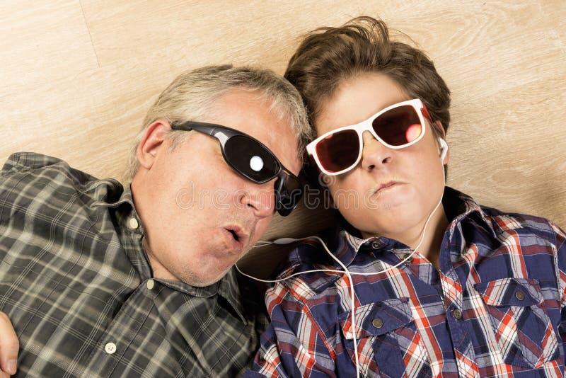 Vader en zoons het luisteren muziek samen royalty-vrije stock afbeelding