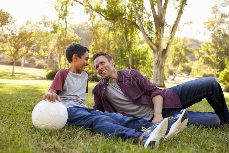 Vader en zoons het ontspannen met voetbalbal in een park, sluit omhoog stock fotografie
