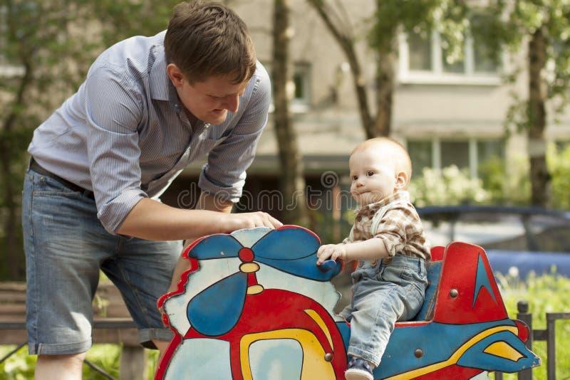 Vader en zoons het spelen bij speelplaats stock foto