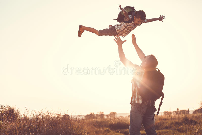 Vader en zoons het spelen in het park in de zonsondergangtijd royalty-vrije stock foto's