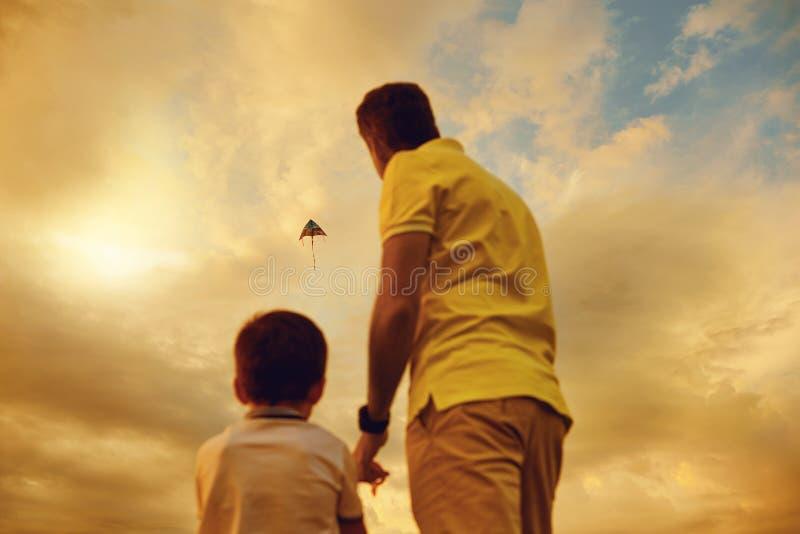 Vader en zoons het spelen met een vlieger bij zonsondergang stock fotografie