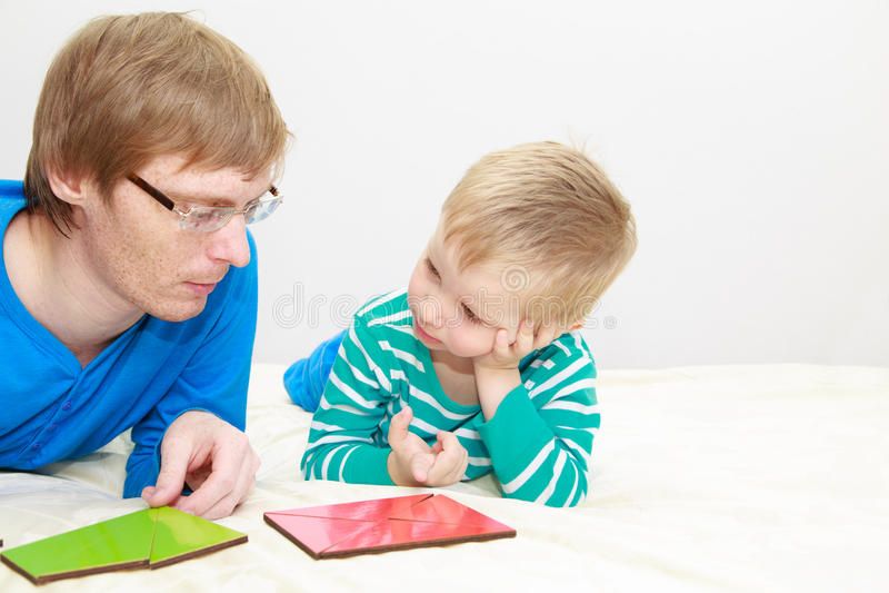 Vader en zoons het spelen met raadsel stock afbeelding