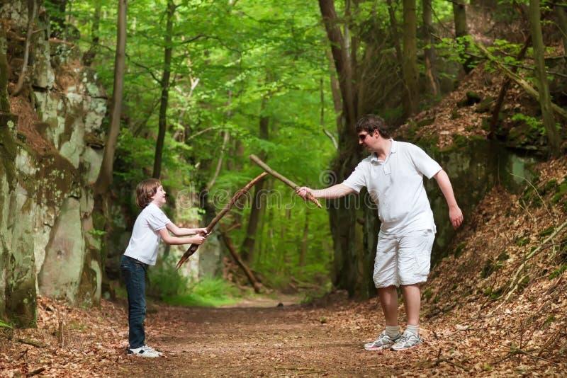 Vader en zoons het spelen met stokken op stijging in park royalty-vrije stock fotografie