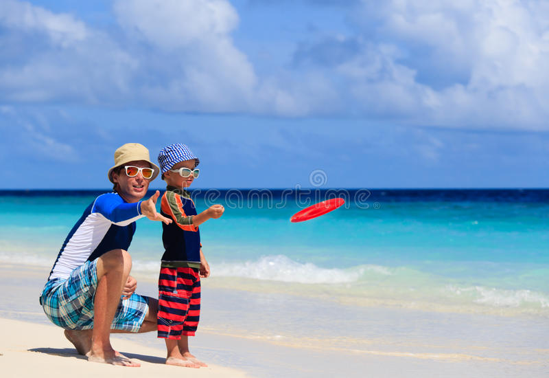 Vader en zoons het spelen met vliegende schijf bij strand royalty-vrije stock afbeelding