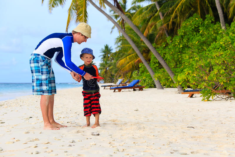 Vader en zoons het spelen met vliegende schijf bij strand royalty-vrije stock afbeeldingen