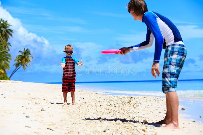 Vader en zoons het spelen met vliegende schijf bij strand stock foto