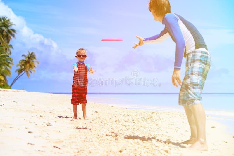 Vader en zoons het spelen met vliegende schijf bij strand royalty-vrije stock fotografie
