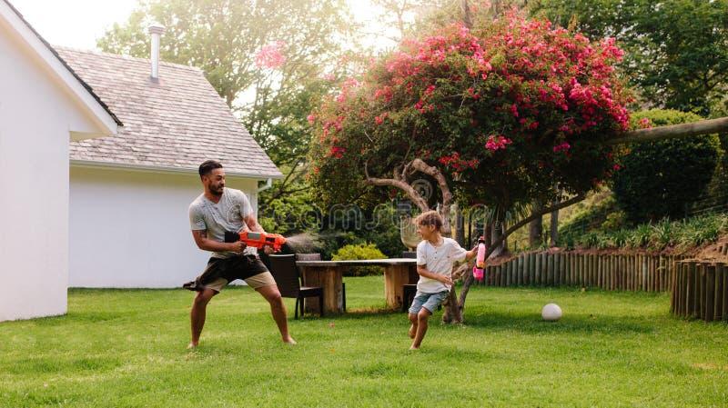 Vader en zoons het spelen met waterkanonnen royalty-vrije stock fotografie