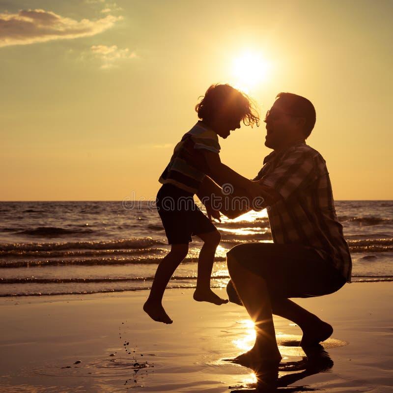 Vader en zoons het spelen op het strand in de zonsondergangtijd royalty-vrije stock afbeeldingen