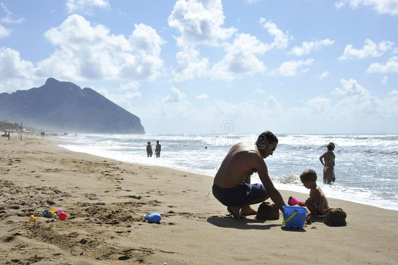 Vader en zoons het spelen op het strand in de zonsondergangtijd Concept vriendschappelijke familie stock afbeeldingen