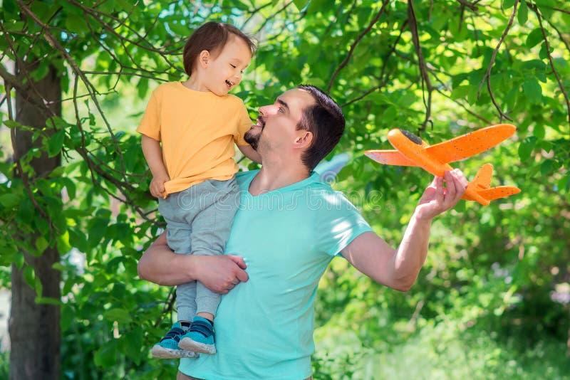 Vader en zoons het spelen samen met oranje vliegtuig in openlucht: de jongen zit op schouder van de mens, zowel glimlachen de pap stock foto