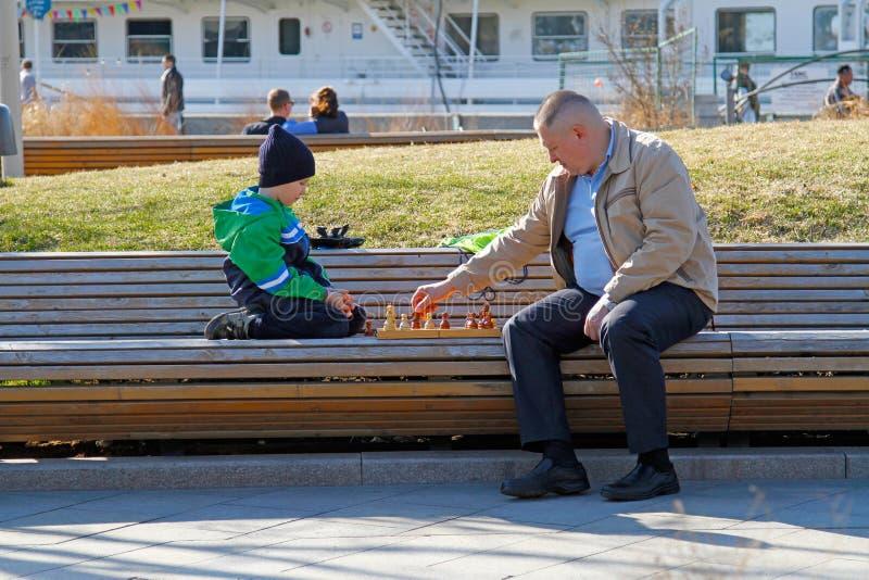 Vader en zoons het spelen schaak in het park Muzeon royalty-vrije stock foto