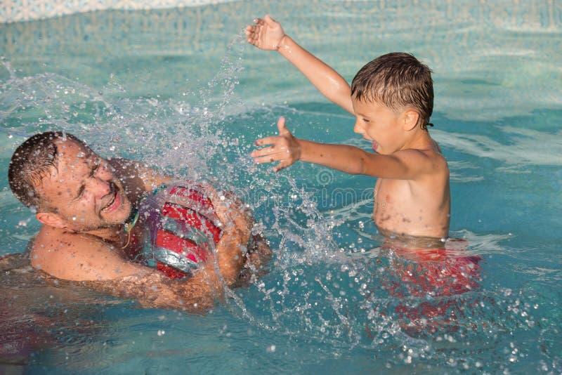 Vader en zoons het spelen in het zwembad in de dagtijd royalty-vrije stock afbeelding