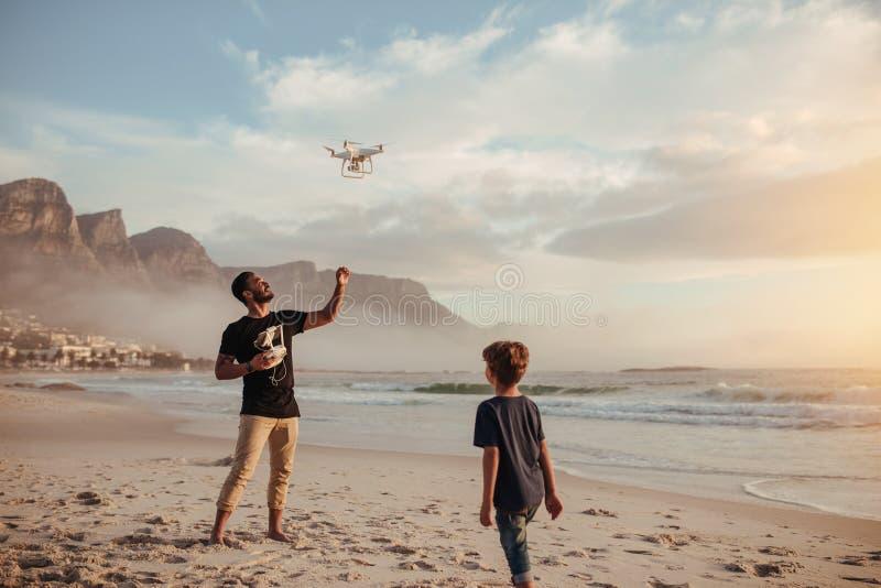 Vader en zoons het werken hommel door afstandsbediening bij strand royalty-vrije stock afbeelding