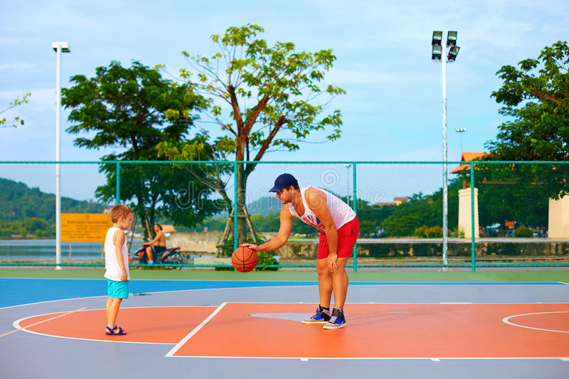 Vader en zoons speelbasketbal op sportgrond stock foto