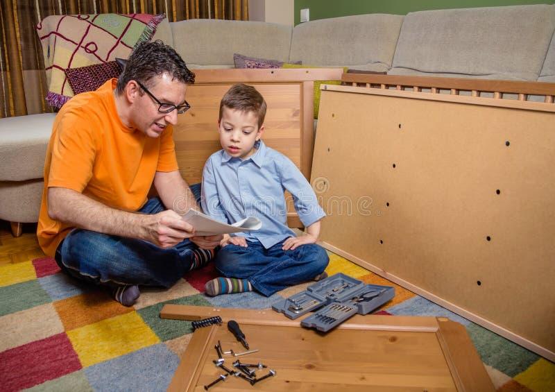 Vader en zoons te assembleren lezingsinstructies royalty-vrije stock foto