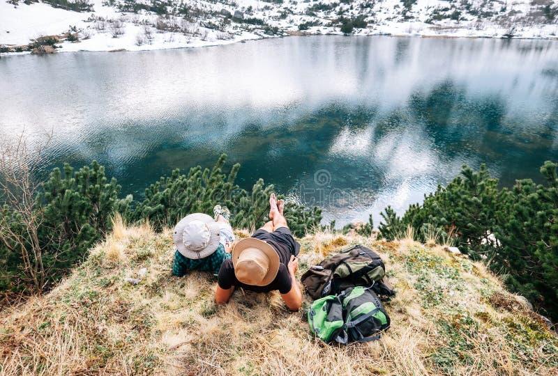 Vader en zoonsbackpackers ontspannen na lange gang dichtbij beauti stock afbeelding