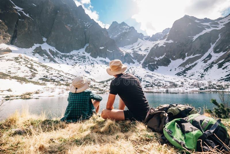 Vader en zoonsbackpackers zitten dichtbij de berg lakeу omringen royalty-vrije stock afbeeldingen