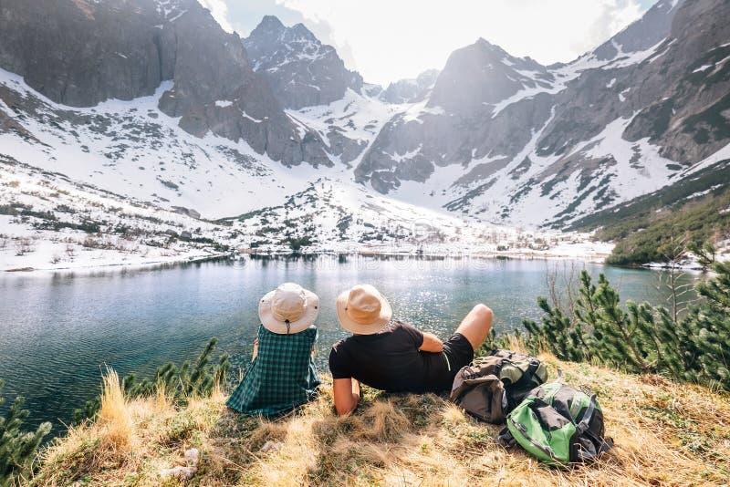 Vader en zoonsbackpackers zitten dichtbij het bergmeer en genieten van stock afbeelding