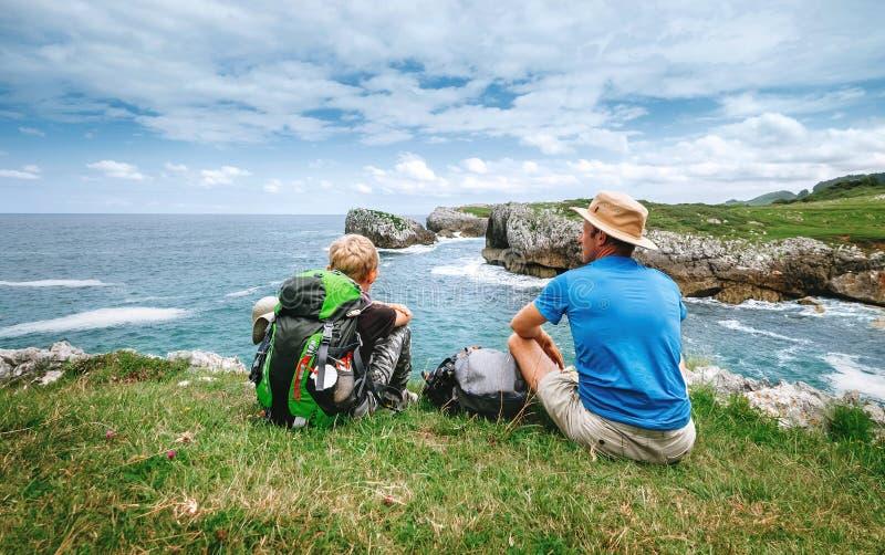 Vader en zoonsbackpackersrust aan de rotsachtige overzeese kant stock afbeelding