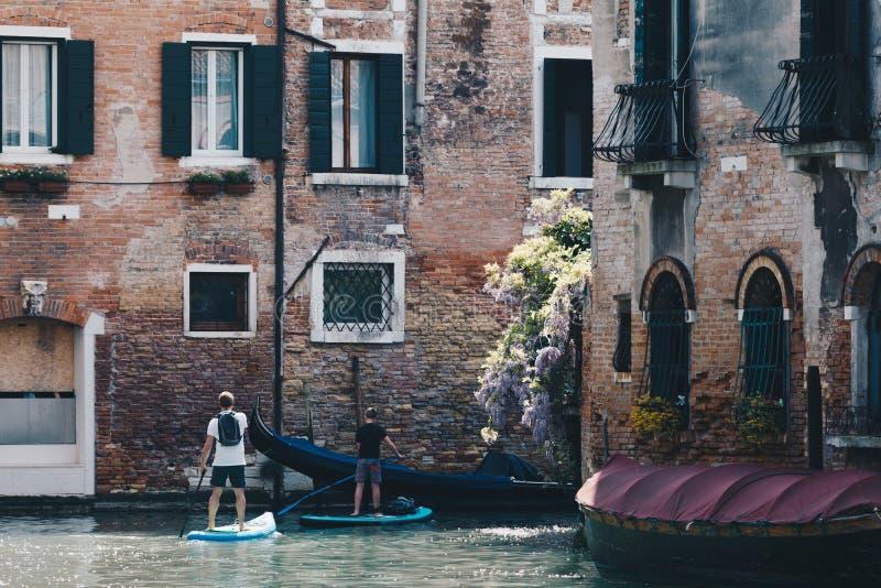 Vader en zoonscanoeing in Venetië met peddel scheept - Alternatieve manier om de Stad te bezoeken - waterwegen in royalty-vrije stock foto's