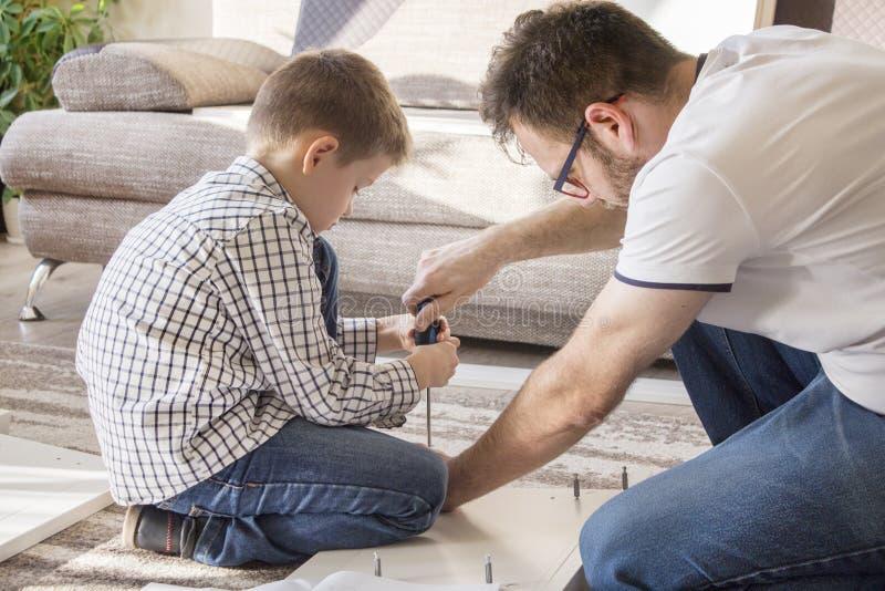Vader en zoonsdraaimeubilair De jongen houdt een schroevedraaier en de vaderhulp om de schroef te schroeven stock foto's