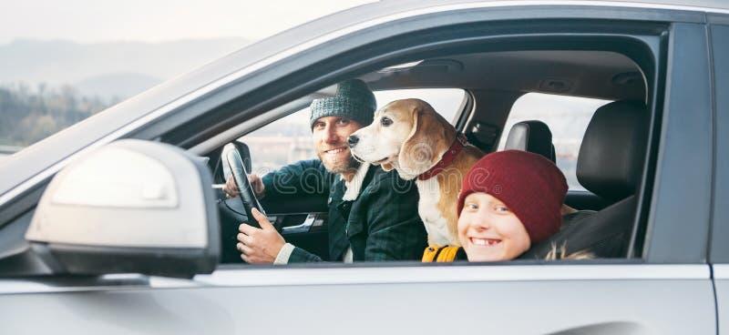Vader en zoonsfamilie die door auto met brakhond reizen Zij zijn royalty-vrije stock fotografie