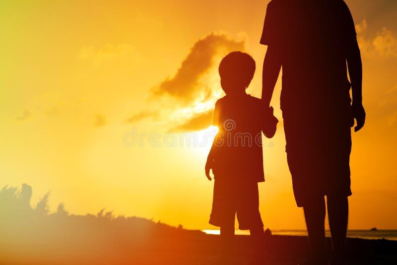 Vader en zoonsholdingshanden bij zonsondergangoverzees royalty-vrije stock afbeeldingen
