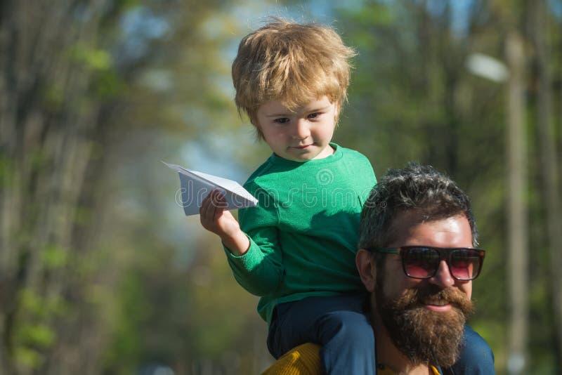 Vader en zoonslanceringsdocument vliegtuig in park, het dromen concept Weinig kind die over het reizen door vliegtuig dromen Er i stock foto