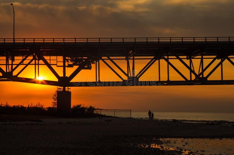 Vader en zoonssilhouet die op strand onder Mackinaw-Brug bij zonsondergang lopen stock foto's