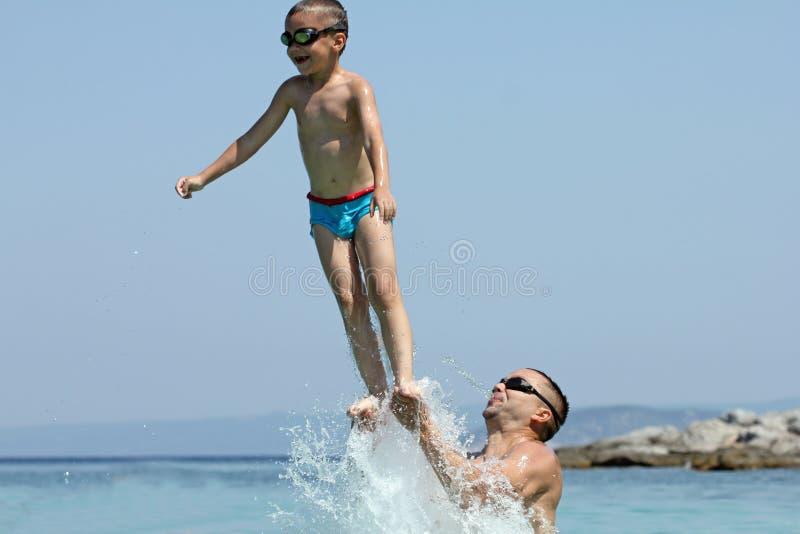 Vader en zoonsspel in water stock afbeeldingen
